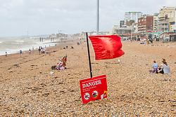© Licensed to London News Pictures. 11/08/2019. Brighton, UK. A handful of people take to the beach in Brighton and Hove as strong gusts of wind continue to his the coast in Brighton and Hove. Warning signs can still be seen on the beach.  Photo credit: Hugo Michiels/LNP