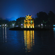 Night photo of the lights of Turtle Tower (also known as Tortoise Tower on a small island in Hoan Kiem Lake in the historical center of Hanoi, Vietnam. City lights in the background light up a deep blue sky.