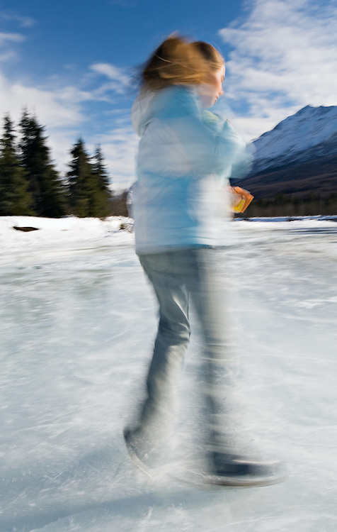 Young girl twirling on figureskates on frozen Eagle River in Chugach State Park with Chugach Mountains backdrop in Southcentral Alaska.  Winter. Afternoon. MR.