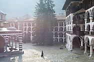A monk in early morning walks in the courtyard of Rila Monastery. The largest and most famous Eastern Orthodox monastery in Bulgaria, it is situated in the southwestern Rila Mountains, 117 km (73 mi) south of the capital Sofia at an elevation of 1,147 m (3,763 ft) above sea level.  It was founded in the 10th century.