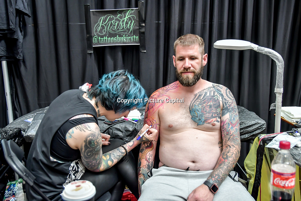 Kristy Peake, tattoo a client at The Great British Tattoo Show, on 26 May 2019, London, UK.