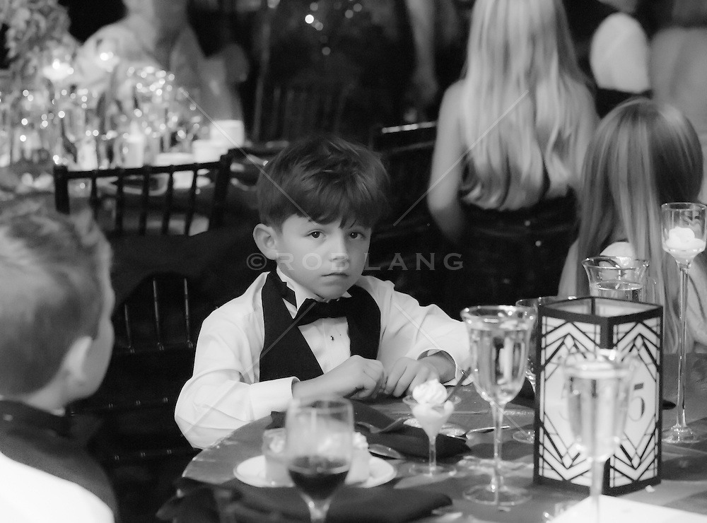 little boy in a tuxedo at a wedding reception