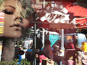 People milling about on the street are reflected in a storefront window as the large face of a model looks out from the store's display.  Located in the Greenwich Village neighborhood of Manhattan, New York City