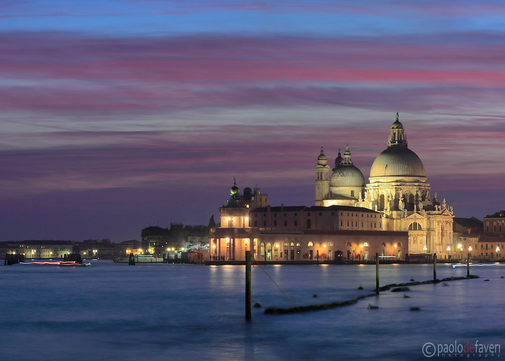 Beautiful stripes of red clouds over the church of Nostra Signora della Salute and Punta della dogana. Taken about 20 minutes after sunset from Riva degli Schiavoni, on an evening of mid January