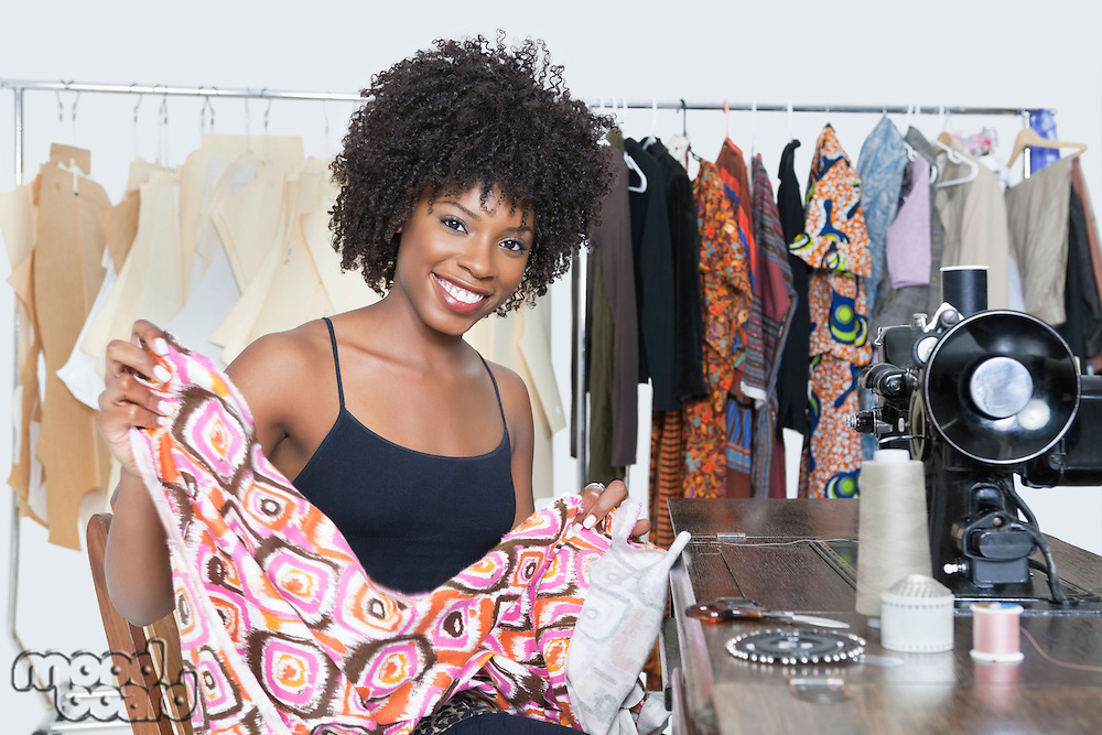 Portrait of an African American female fashion designer holding pattern cloth