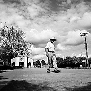 An old man walks across the plaza of a small town under paramilitary control but surrounded by FARC rebels, La Dorada, Putumayo.<br />