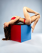Fashion photo of swimsuit model in dramtic reclining pose on top of red and blue cube.  Model Rachael Campbell. Photographer Gerard Harrison, Image Theory Photoworks.