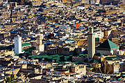 Al-Kairouine Mosque and University, Fez Medina, Morocco, 2018-02-03.<br /> <br /> View over the old Fez Medina, with the Al-Karaouine Mosque and University (building with green tiled roof and white Minaret) and the Zawiya Moulay Idriss II (building to the right of Karaouine, with tall minaret and pyramid roof).<br /> <br /> Established at the very beginnings of Morocco's oldest imperial city, the University of Al-Karaouine (also written as Al-Quaraouiyine and Al-Qarawiyyin) was founded in 859 and is considered by Unesco and the Guinness Book of World Records to be the oldest continually operating university in the world.<br /> <br /> Located in the heart of the old city, the complex is composed of a mosque, university and library, and is connected to the labyrinth of interconnecting streets and alleyways on all four sides. Its ceramic green tiled roofs take centre stage over Fez's urban sprawl from any viewpoint over the city.