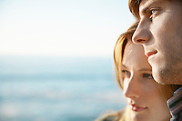 Young woman leaning on young man close up ocean and sea in background