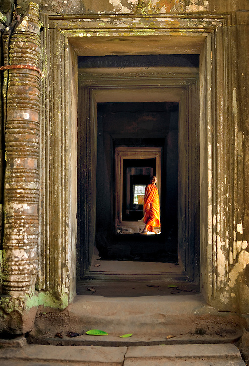 Angkor Ta Prohm, perspective view down a corridor, orange-robed monk pausing in the distance.