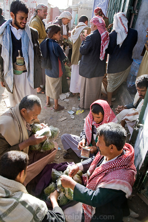 Qat sellers make transactions and count money from their day's sales at a qat market near Rock Palace, near Sanaa, Yemen.