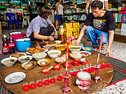 """05 SEPTEMBER 2017 - BANGKOK, THAILAND:  People set up their Hungry Ghost Day banquets in Bangkok's Chinatown. The Ghost Festival is a Buddhist and Taoist holy day celebrated on the 15th day of the 7th lunar month. It is primarily celebrated in China and Chinese communities outisde China. In Thailand, it's celebrated in Thai-Chinese communities in Bangkok, Phuket and Chiang Mai.  On that day ghosts and spirits, including those of the deceased ancestors, come out from the lower realm to visit the living. Families prepare elaborate banquets for the spirits and burn """"ghost money"""" for the spirits to use in the other realm. It is a day for venerating dead relatives.     PHOTO BY JACK KURTZ"""