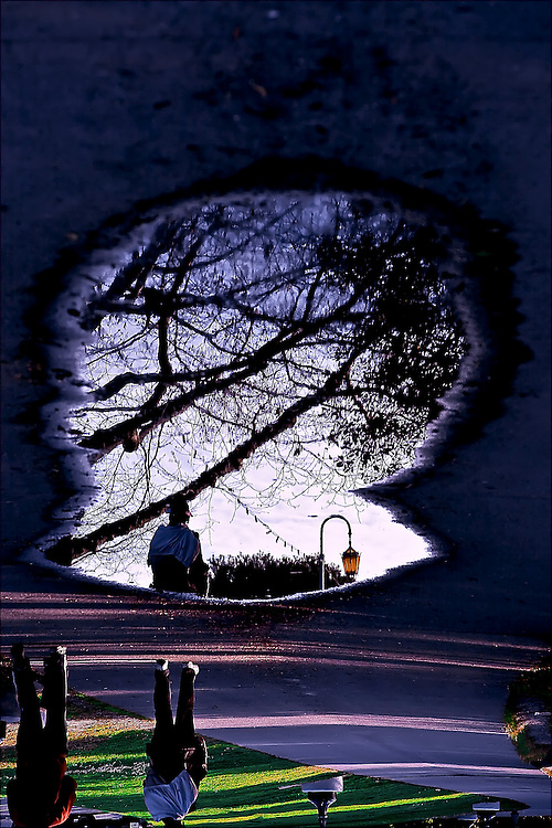 Reflections of lake walkers in puddle at Lake Merritt in Oakland, CA.  Copyright 2008 Reid McNally.