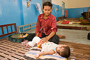 26 JUNE 2006 - SIEM REAP, CAMBODIA: A woman tends to her baby in the woman's dorm at Handicapped International in Siem Reap, Cambodia. Handicapped International helps Cambodians maimed by mines and unexploded ordinance as well as traffic accidents and disease adjust to a life without limbs. Cambodians are still wrestling with the legacy of the war in Vietnam and subsequent civil wars. At one time it was the most heavily mined country in the world and a vast swath of Cambodia, along the Thai-Cambodian border, is still mined. In 2004, more than 800 people were killed by mines and unexploded ordinance still found in the countryside.  Photo by Jack Kurtz