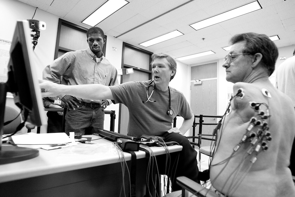 Dr. Todd Kuiken M.D. Ph.D, middle, and research assistant Bolu Ajiboye, left, watch the screen of a computer attached to surface electrodes attached to artificial arm recipient Jesse Sullivan at Rehabilitation Institute of Chicago.  The electrodes detect EMGs, or electrical activity of the muscles.  Sullivan, of Dayton, Tennessee, was the first patient to undergo the surgery to enhance use of an artificial arm.  Sullivan lost both arms on the job as a lineman for a Tennessee power company who accidentally touched a high tension wire carrying 7400 volts.  The accident cost Sullivan both of his arms up to the shoulders. The nerves that once controlled Sullivan's left arm were surgically implanted into his chest muscles since he had no arm muscles at all.  He was outfitted with a Boston Digital Arm and the contacts in the socket of the prosthesis were positioned where the prosthetist finds the strongest EMG signal.  Sullivan currently has control over three different mechanical arm functions and is being tested for other sites for contacts as the nerves continue to innervate the muscles.  The arm feels so natural to him that he once yanked off his mechanical hand trying to start the lawnmower.  On his right side Sullivan uses an older body-powered mechanical arm with a split hook hand..