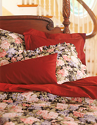 bed with dark floral patterned sheets