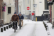 Twee mannen fietsen in de sneeuw door de Korte Smeestraat in Utrecht.<br /> <br /> Two man are cycling in the snow at the Korte Smeestraat Utrecht.