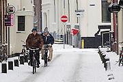 Twee mannen fietsen in de sneeuw door de Korte Smeestraat in Utrecht.<br /> <br /> Two man are cycling in the snow at the Korte Smeestraat Utrecht.