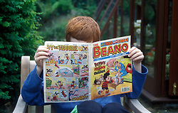 9 year old boy reading The Beano comic UK. MR