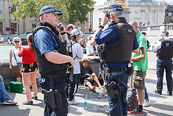 """An alleged pickpocket sits on the ground, his hands cuffed after being chased down by a Romanian street performer working on the North Terrace of Trafalgar Square. Street performers demanded that Romanian pickpockets desist from """"working"""" on the North Terrace of Trafalgar Square where they steal from crowds watching the street entertainers. London, August 02 2019."""