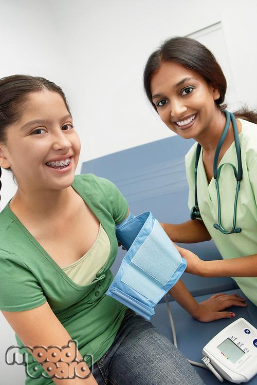 Female doctor taking girls blood pressure