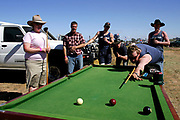 """Festival-goers play a game of outdoor pool at the annual Deniliquin Ute Muster in Deniliquin, Australia. A """"ute"""" is a term used in Australia for a utility vehicle, popular in the rural areas and used for farming and other work needs."""