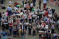 """© Licensed to London News Pictures . 16/08/2015 . Manchester , UK . People in a crowd of several hundred , holding up placards naming regions from across Greater Manchester , at a """" Peterloo """" memorial at the site of St Peter's Field , where fifteen people were killed during a cavalry charge on a democracy protest , 196 years ago (16th August 1819) . Photo credit : Joel Goodman/LNP"""