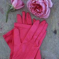 Pair of folded bright pink elbow-length satin ladies gloves lying on marbled slate with two pale pink roses