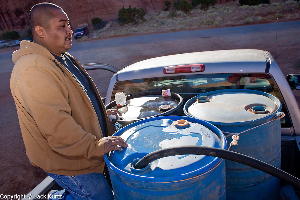 22 OCTOBER 2007 -- MONUMENT VALLEY, UT: ORLANDO CLY, a Navajo Indian living on the Navajo Reservation in northern Arizona, fills 50 gallon barrels with potable water at the well at Goulding's Trading Post near Monument Valley, UT. The well at Goulding's was first dug by Seventh Day Adventists missionaries and is the only source of clean, free water for miles around. More than 30 percent of the homes on the Navajo Nation, about the size of West Virginia and the largest Indian reservation in the US, don't have indoor plumbing or a regular supply of domestic water. Many of these homes have to either buy water from commercial vendors or haul water from public wells. A Federal study showed that the total cost of hauling water was about $113 per 1,000 gallons. A Phoenix household, in comparison, pays just $5 a month for up to 7,400 gallons of water. The lack of water on the reservation means the Navajo are among the most miserly users of water in the United States. Families that have to buy or haul water use only about 15 gallons of water per day per person. In Phoenix, by comparison, the average water use is about 170 gallons per day.  Photo by Jack Kurtz