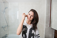 Portrait of beautiful woman applying makeup in bathroom