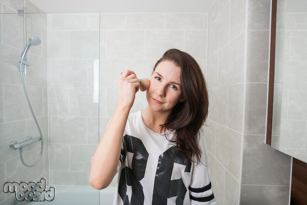 Portrait of beautiful woman applying makeup in bathroom