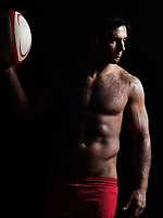 one caucasian sexy topless man portrait holding  a rugby ball on studio black background