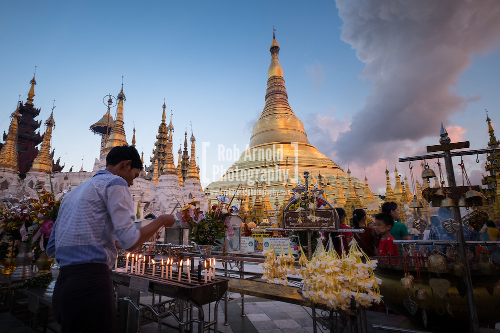 A man lighting a candle during sunset at the Shwedagon Pagoda in Yangon, Myanmar.