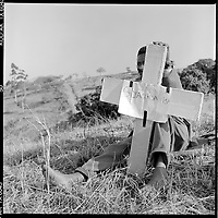 """""""We are selling them"""" A man sells concrete cast crosses for economy minders burials in the Shembe cemetary at KwaMashu, 1998. The founder Isaiah Shembe is seen as a spiritual descendent of Moses and Jesus, and th church embraces traditional Zulu values and customs. Photo Greg Marinovich"""
