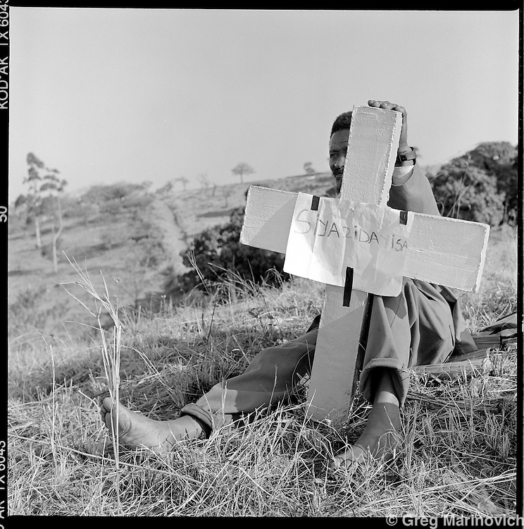 """We are selling them"" A man sells concrete cast crosses for economy minders burials in the Shembe cemetary at KwaMashu, 1998. The founder Isaiah Shembe is seen as a spiritual descendent of Moses and Jesus, and th church embraces traditional Zulu values and customs. Photo Greg Marinovich"
