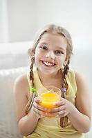 Portrait of happy young girl drinking orange juice