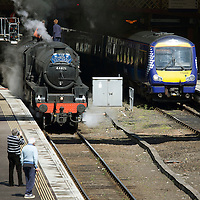 The Old and the new pictured at Perth Railway Station this afternoon as the 'The Cathedrals Explorer' steam train stocks up with coal and water before continuing onto Fort William...13.05.14<br /> Picture by Graeme Hart.<br /> Copyright Perthshire Picture Agency<br /> Tel: 01738 623350  Mobile: 07990 594431