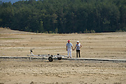 couple looking at an empty boat trailer at a dried up lake shore