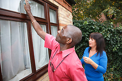 Elderly black man with white woman carer cleaning windows