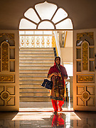 "08 FEBRUARY 2015  BANGKOK, THAILAND: A woman walks into the Darbar Sahib (prayer hall) at Gurdwara Siri Guru Singh Sabha, the Sikh temple in Bangkok. Thailand has a small but influential Sikh community. Sikhs started coming to Thailand, then Siam, in the 1890s. There are now several thousand Thai-Indian Sikh families. Gurdwara Siri Guru Singh Sabha was established in 1913. Construction of the current building, adjacent to the original Gurdwara (""Gateway to the Guru""), started in 1979 and was finished in 1981. The Sikh community serves a daily free vegetarian meal at the Gurdwara that is available to people of any faith and background.    PHOTO BY JACK KURTZ"