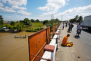 Mekong Delta. Buddhist monk meditating on a bridge across a river arm, a traditional rowing boat passing underneath.
