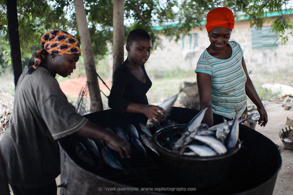 Patience Diaba (right) prepares smoked fish at her home in Dabala Junction in the Volta Region of Ghana and sells it at a nearby market. Her participation in a 'Banking on Change' Village Savings and Loan Association (VSLA) has helped her expand her business. She is assisted by her cousins, Barbara Diaba (centre), and Peace Ayigbor.