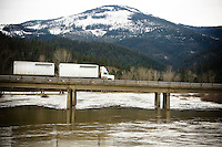 JEROME A. POLLOS/Press..A semi-truck drives west Monday over the Coeur d'Alene River in Cataldo on Interstate-90 where the water level was receding after rising within a few inches of flood stage Monday afternoon following a flood warning issued by National Weather Service.