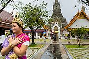 "23 SEPTEMBER 2013 - BANGKOK, THAILAND:  Tourists pose for pictures dressed in costumes of the Royal Thai court circa 1800 in front of the central prang at Wat Arun. The outstanding feature of Wat Arun is its central prang (Khmer-style tower). The world-famous stupa will be closed for three years to undergo repairs and renovation along with other structures in the temple compound. This will be the biggest repair and renovation work on the stupa in the last 14 years. In the past, even while large-scale work was being done, the stupa used to remain open to tourists. It may be named ""Temple of the Dawn"" because the first light of morning reflects off the surface of the temple with a pearly iridescence. The height is reported by different sources as between 66,80 meters and 86 meters. The corners are marked by 4 smaller satellite prangs. The temple was built in the days of Thailand's ancient capital of Ayutthaya and originally known as Wat Makok (The Olive Temple). King Rama IV gave the temple the present name Wat Arunratchawararam. Wat Arun officially ordained its first westerner, an American, in 2005. The central prang symbolizes Mount Meru of the Indian cosmology. The temple's distinctive silhouette is the logo of the Tourism Authority of Thailand.          PHOTO BY JACK KURTZ"