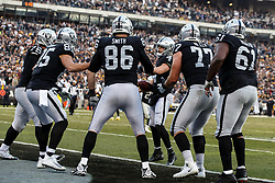 OAKLAND, CA - DECEMBER 09: Tight end Lee Smith #86 of the Oakland Raiders celebrates with quarterback Derek Carr #4 and teammates after catching a pass for a touchdown against the Pittsburgh Steelers during the fourth quarter at the Oakland Coliseum on December 9, 2018 in Oakland, California. The Oakland Raiders defeated the Pittsburgh Steelers 24-21. (Photo by Jason O. Watson/Getty Images) *** Local Caption *** Lee Smith; Derek Carr