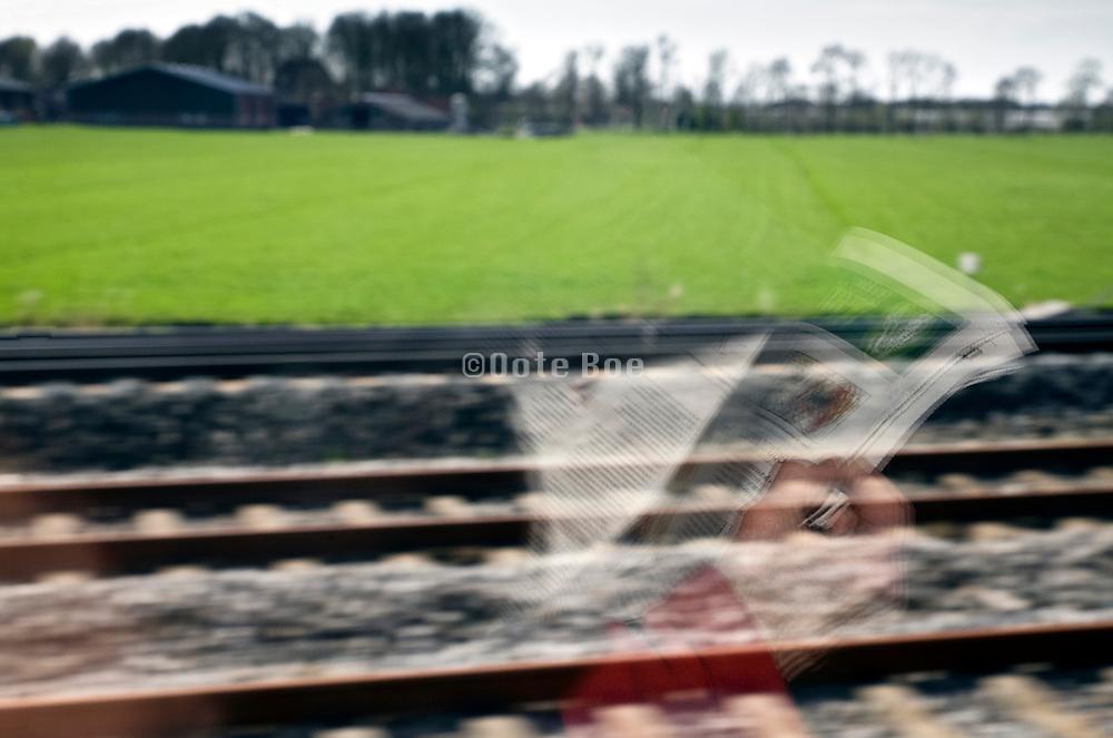 reading reflection in train window while traveling through Dutch rural landscape near Utrecht