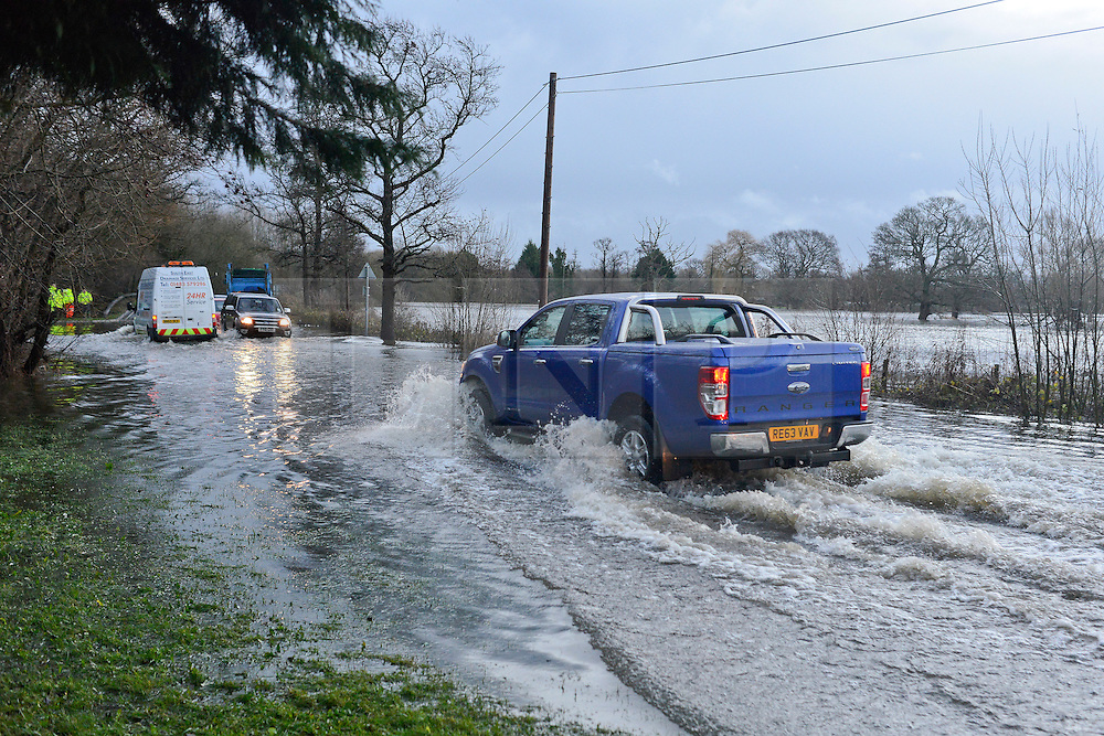 © Licensed to London News Pictures. 03/01/2014. Jacobs Well, UK Cars pass through flood water created by the River Mole bursting it's banks at Jacobs Well in Surrey today 3rd January 2013. Floods an heavy rain are continuing to effect travel and people across the country today. Photo credit : Stephen Simpson/LNP