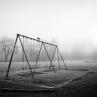 An empty swingset in an open foggy field.