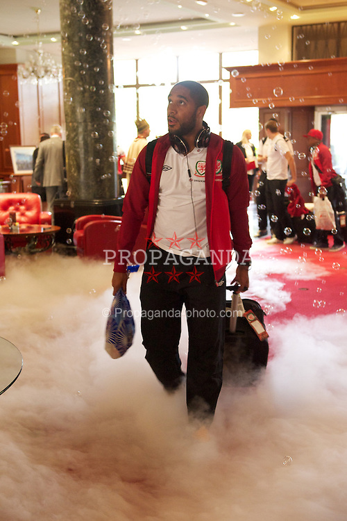 NOVI SAD, SERBIA - Monday, September 10, 2012: Wales' Ashley Williams walks through dry ice and bubbles as the Hotel Park welcomes the players to Novi Sad ahead of the 2014 FIFA World Cup Brazil Qualifying Group A match against Serbia. (Pic by David Rawcliffe/Propaganda)
