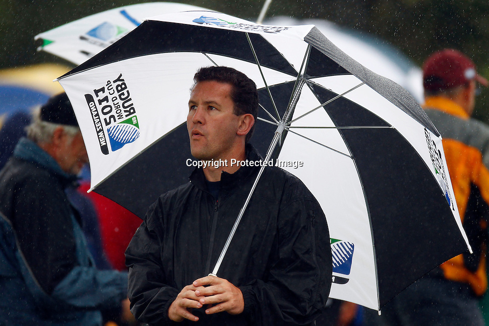 A spectator takes shelter under an umbrella during the HRV Cup match between the Northern Knight v Wellington Firebirds. Men's domestic one day cricket. Blake Park, Mt Maunganui, New Zealand. 4 January 2012. Ella Brockelsby / photosport.co.nz